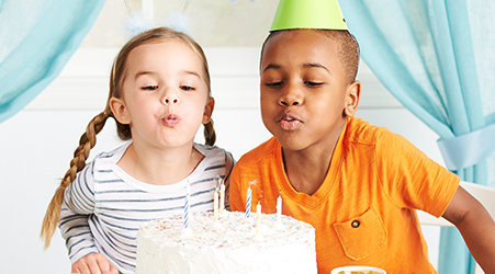 Kids blowing out candles on birthday cake